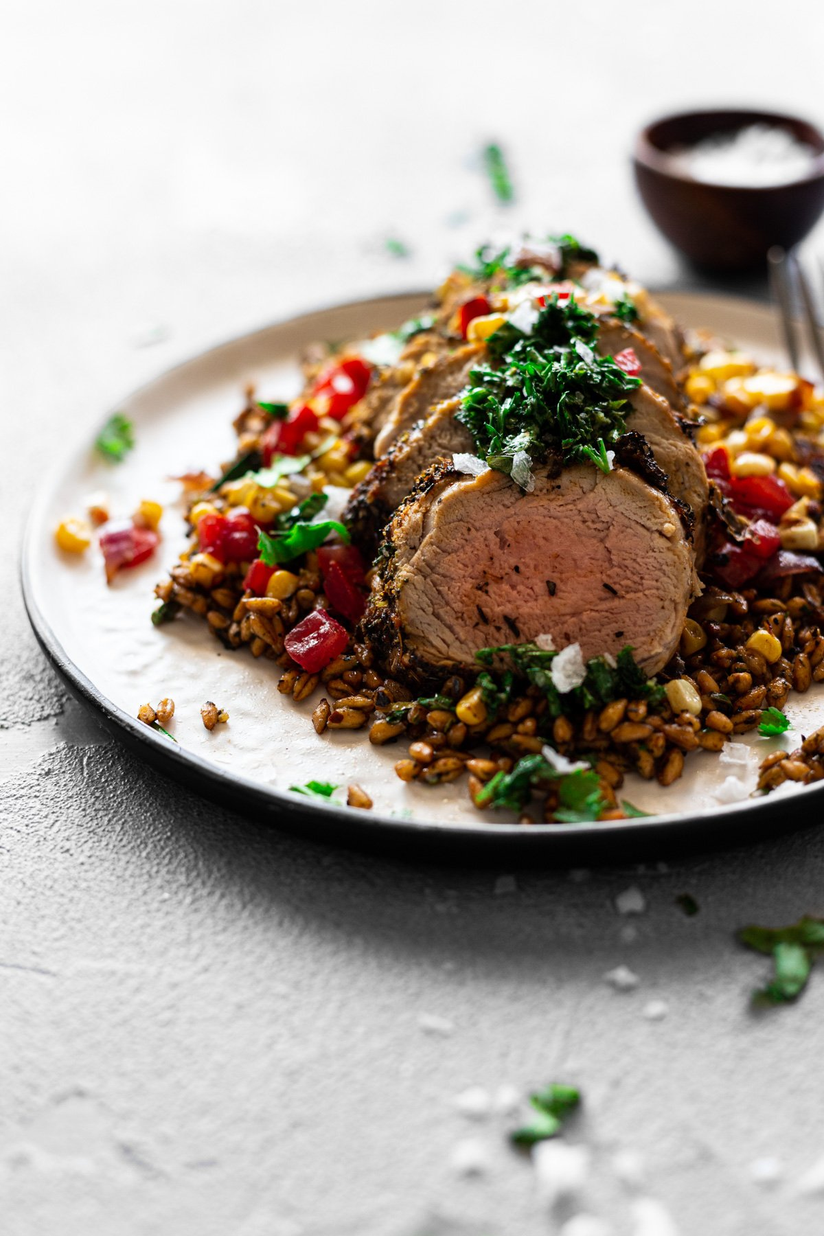 a plate with chimichurri air fryer pork tenderloin with charred corn and farro salad