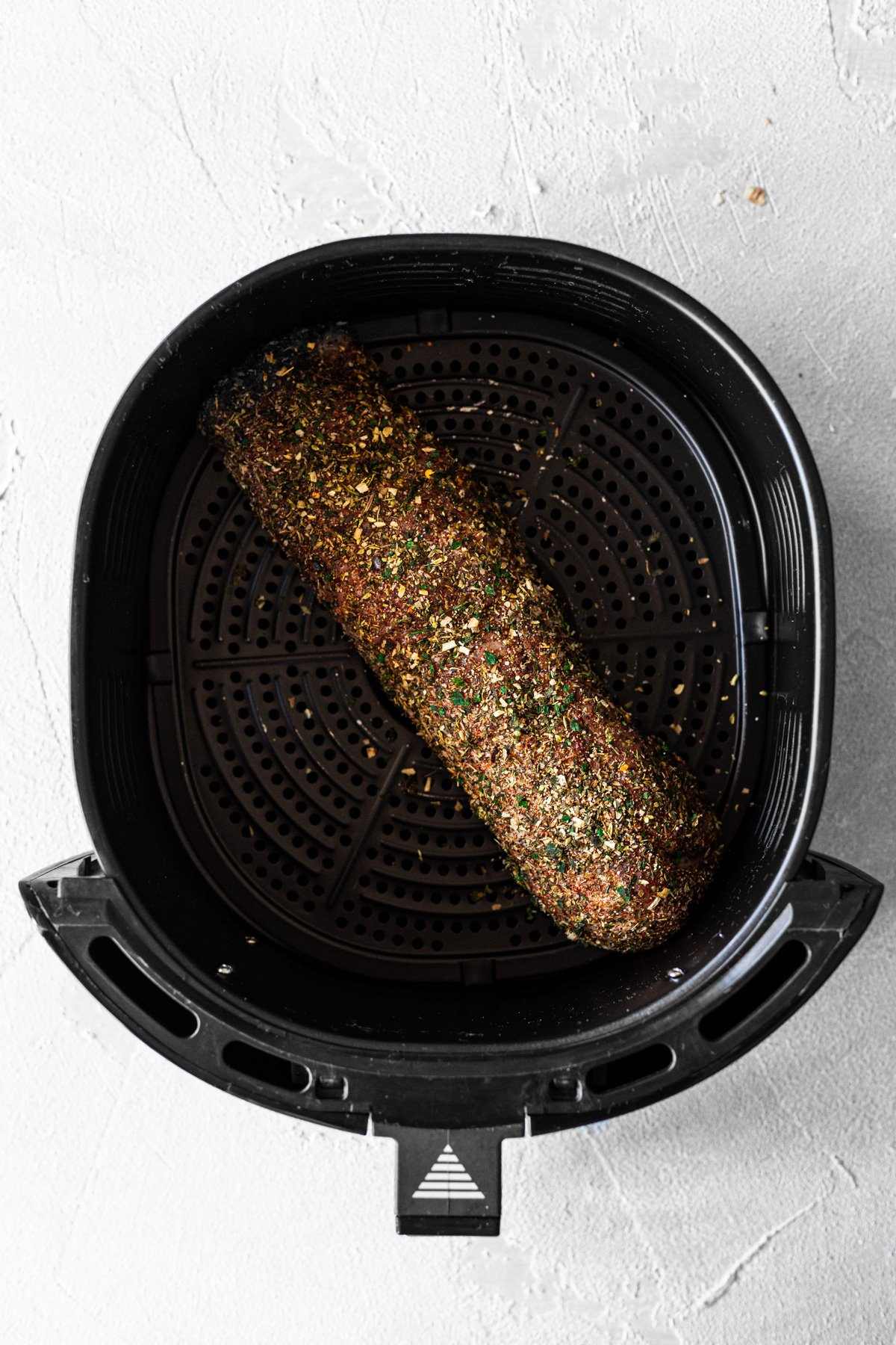 Pork tenderloin coated in dry chimichurri rub and inside an air fryer basket