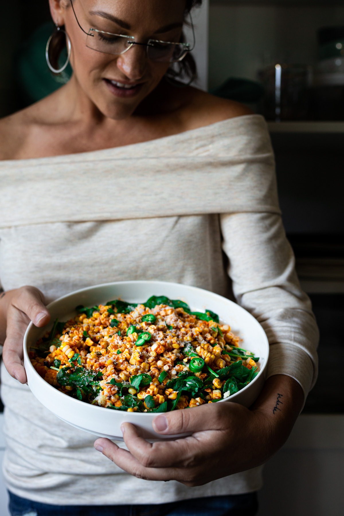Karly Gomez holding a bowl of corn and arugula salad with roasted red pepper sauce
