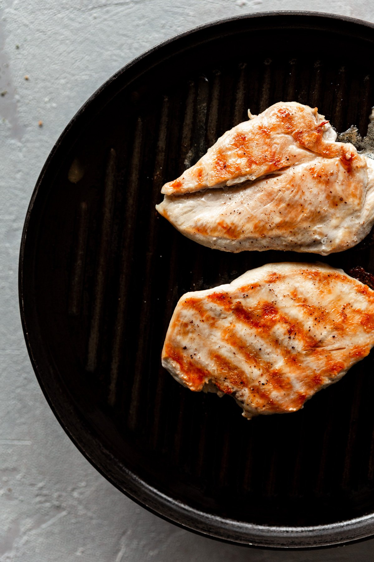 grill pan with two grilled chicken breast, grill marks facing up