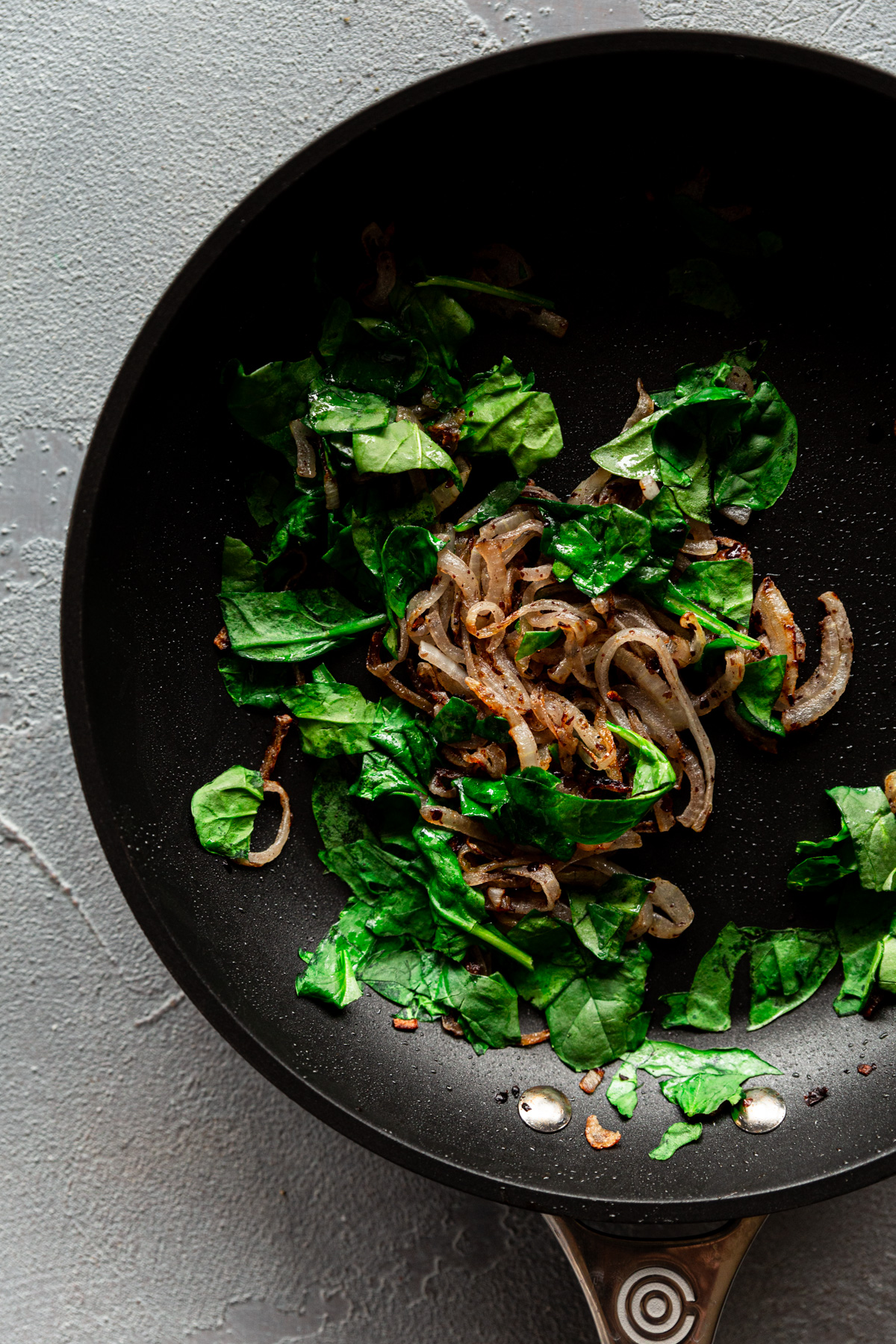a skillet with sumac caramelized onions and wilted spinach
