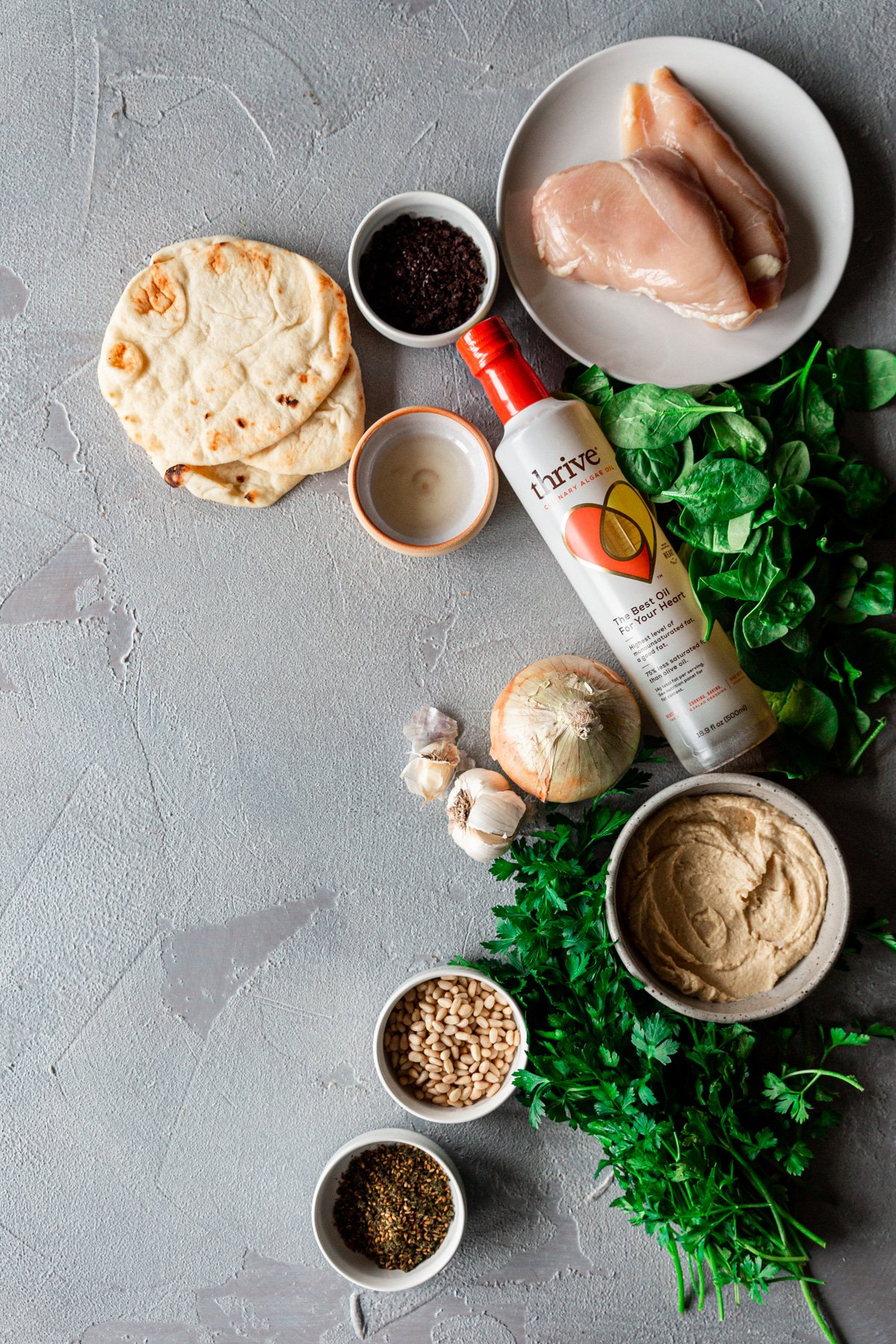 ingredients for grilled chicken flatbread with za'atar hummus, sumac caramelized onions, and spinach salad