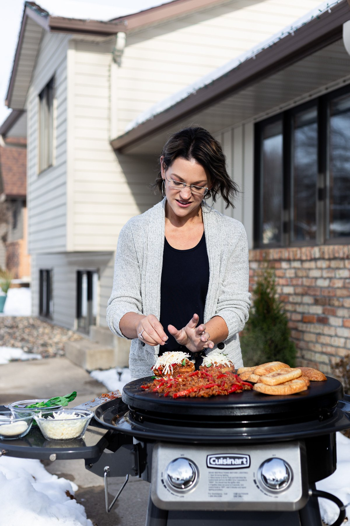 karly gomez preparing sausage and peppers sliders on an outdoor griddle