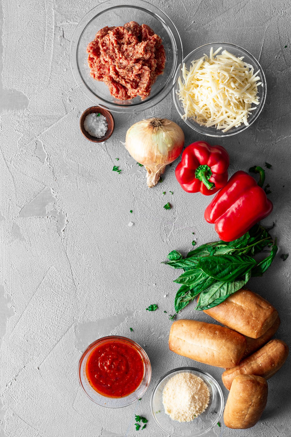 ingredients for sausage and peppers sloppy joe sliders on a grey background