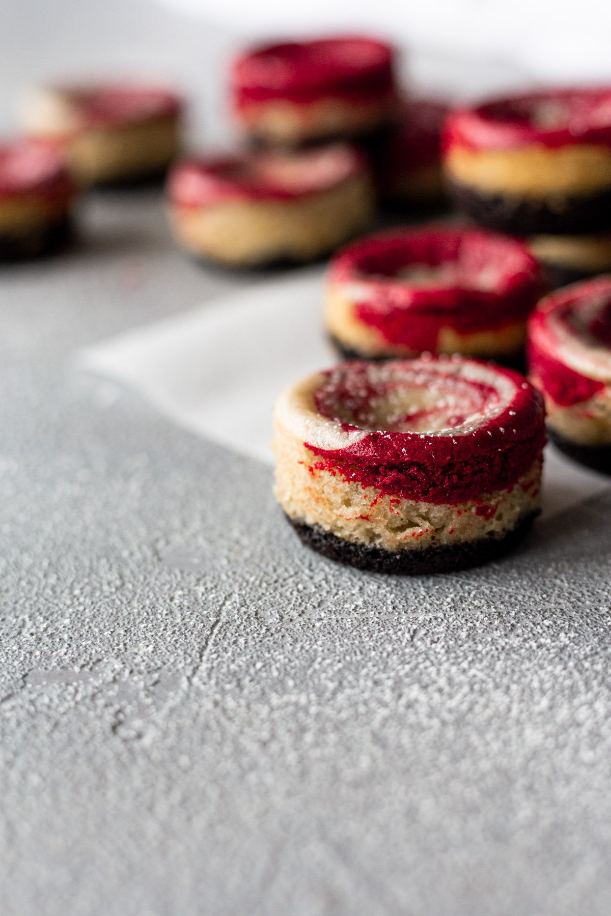 mini red velvet vegan cheesecakes scattered on a grey backdrop
