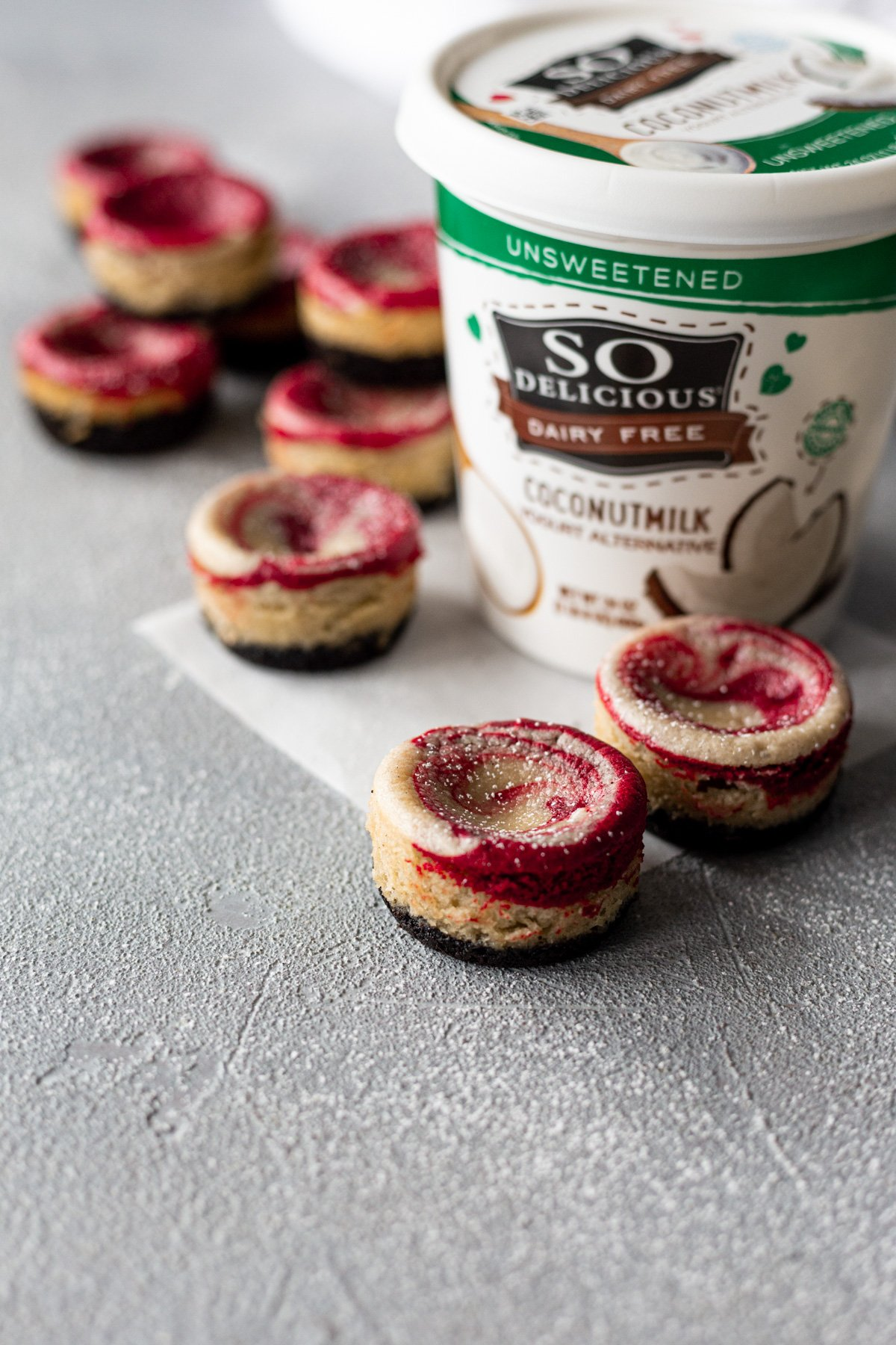 mini red velvet vegan cheesecakes with a carton of so delicious coconutmilk yogurt