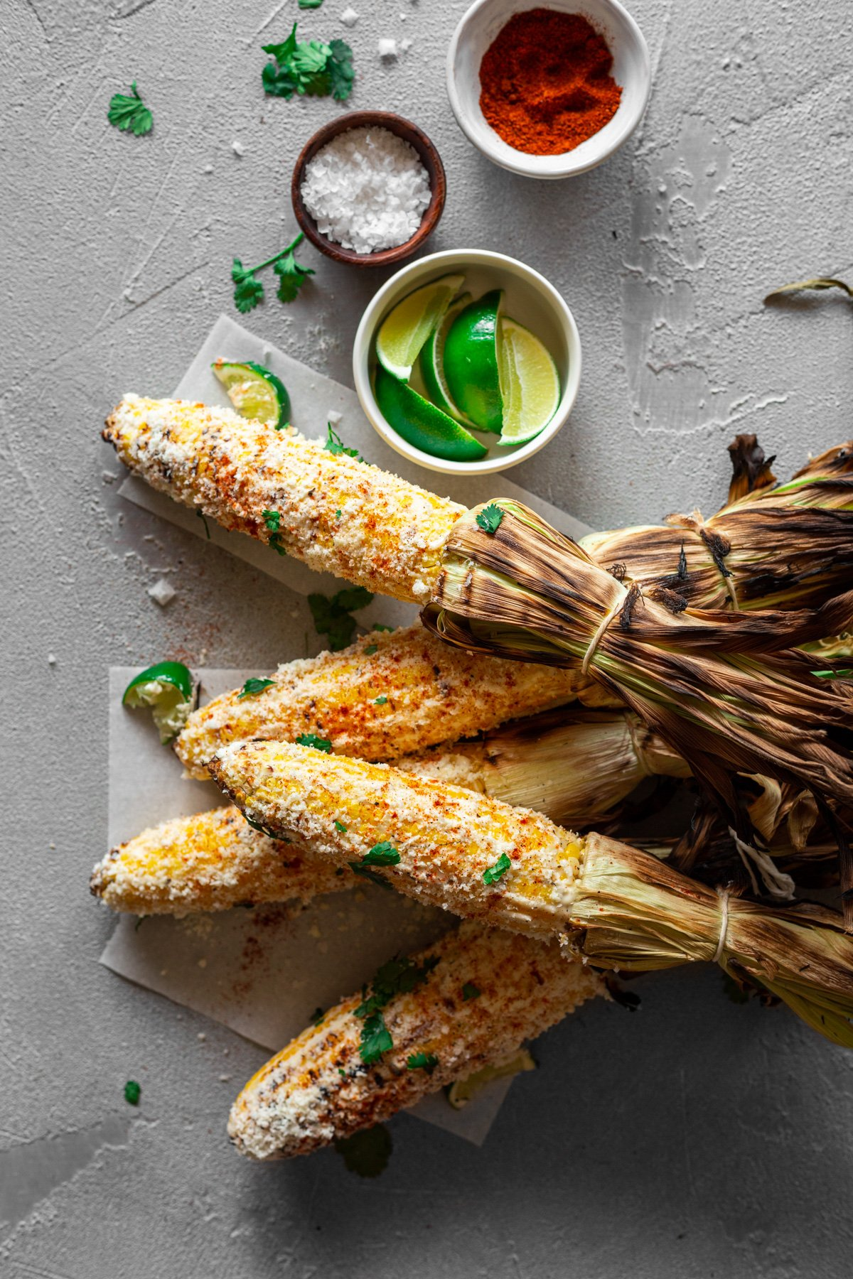 mexican street corn on a gray backdrop with limes, chili powder, and flake salt