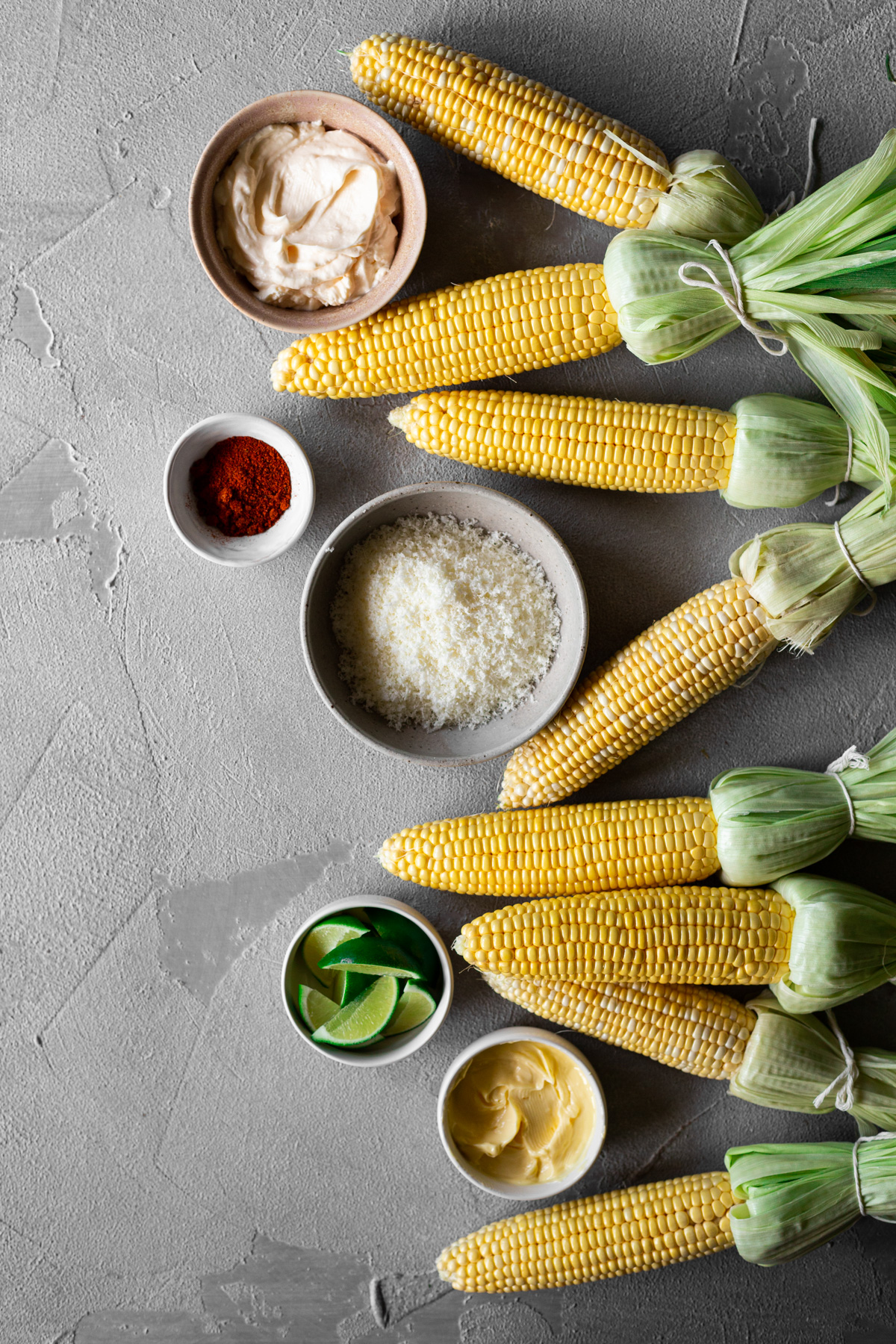 ingredients for mexican street corn: mayo, grated cheese, chili powder, butter, limes