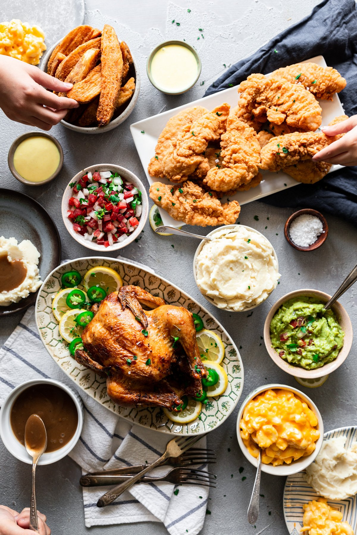 overhead tablescape of chicken, sides dishes, condiments, and hands grabbing food