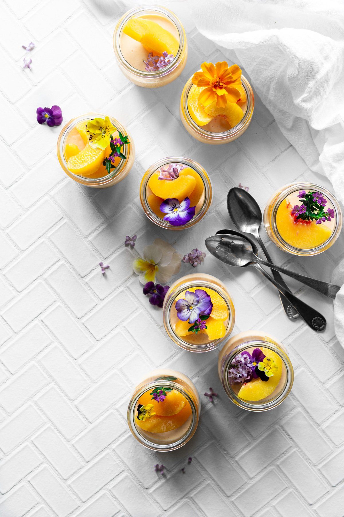 overhead view of eight jars of peach jello salad with peach slices and edible flowers