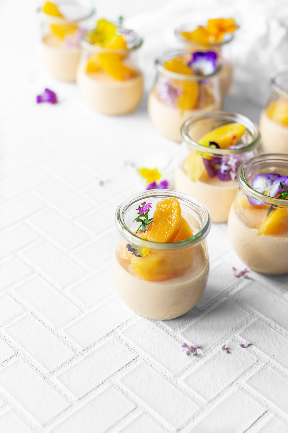 jars of peach jello salad with sliced peaches and edible flowers