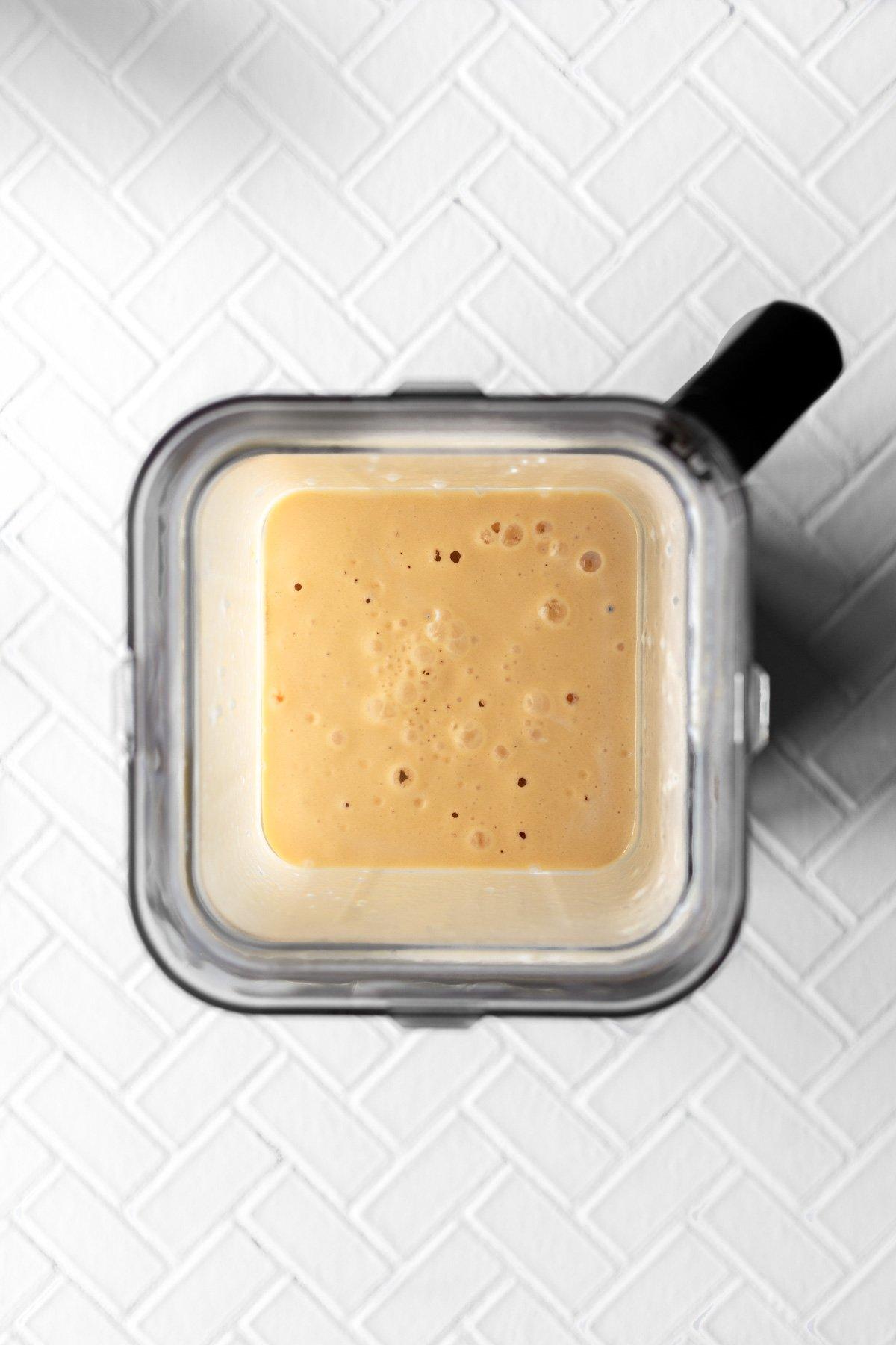 blender jar with blended peach jello salad inside