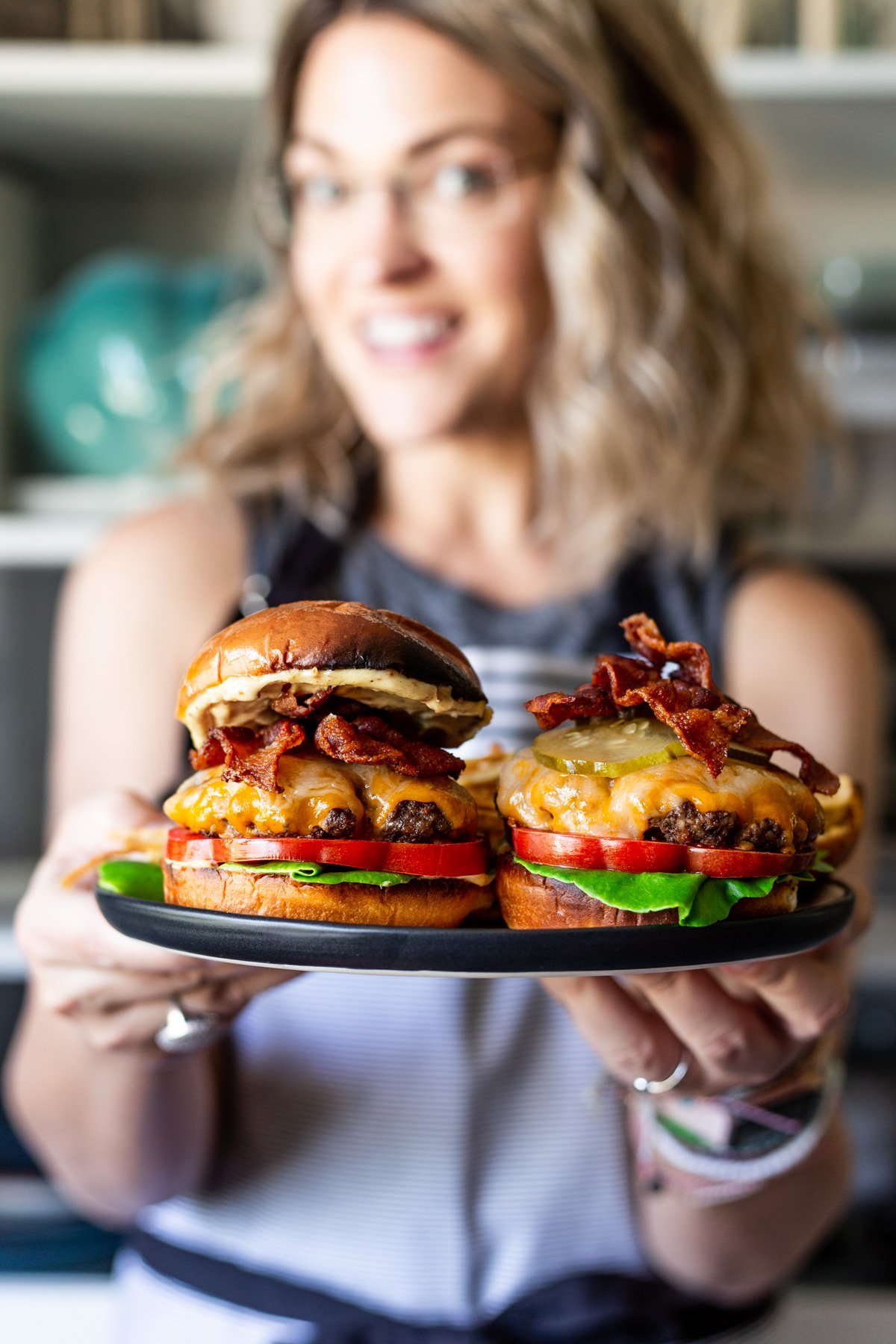 Karly Gomez holding a plate with two bacon smash burgers with bacon aioli