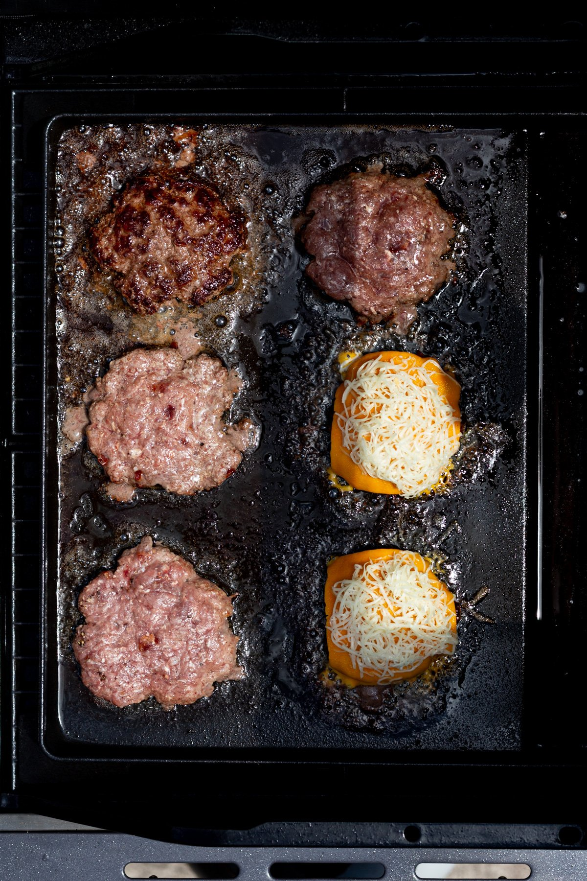 Bacon smash burger recipe cooking on griddle of gas grill, two with cheese on them