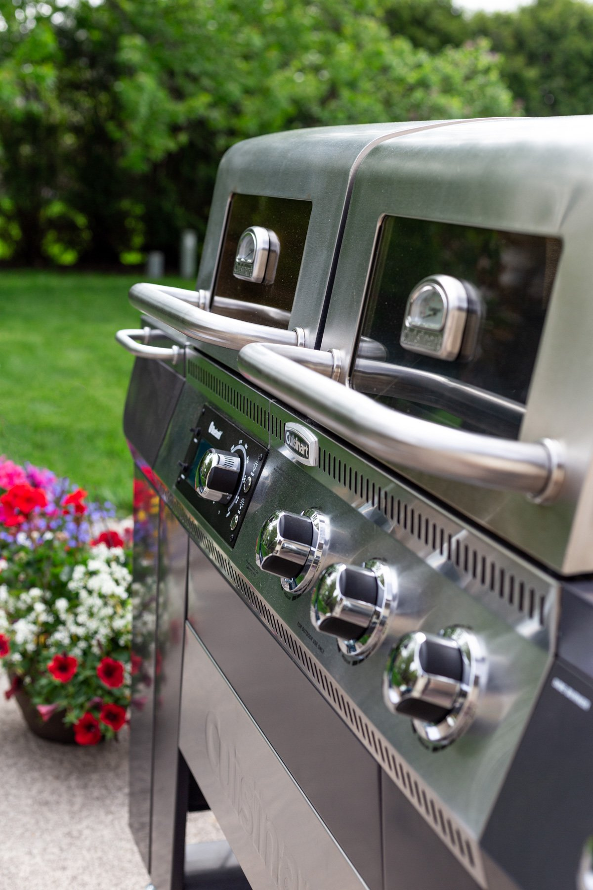 Angled view of Cuisinart Twin Oaks Pellet & Gas Grill with backyard in the distance