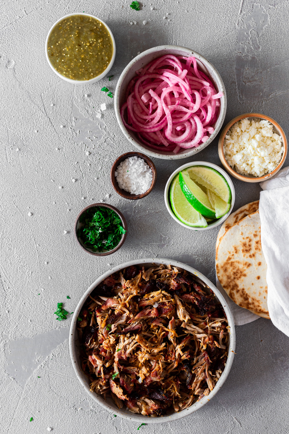 ingredients for cochinita pibil tacos in bowls on a gray background