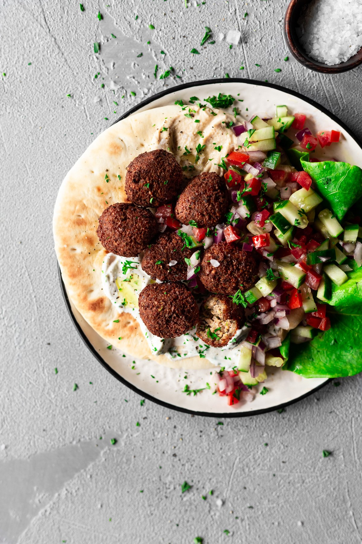 closeup of falafel on pita with hummus, tzatziki, and israeli salad