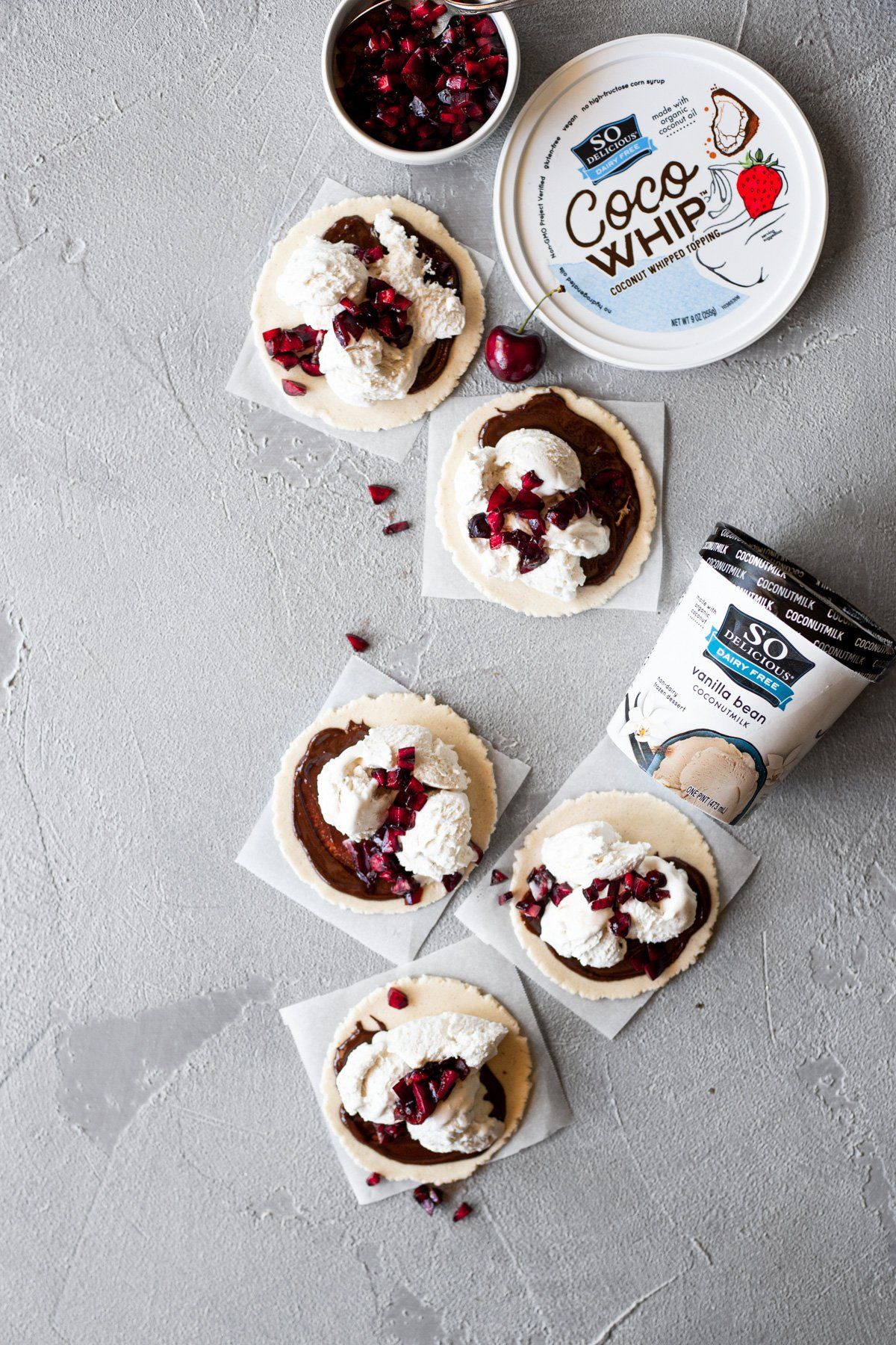 edible cookie dough dessert tacos with so delicious dairy free frozen dessert and cocowhip in the background