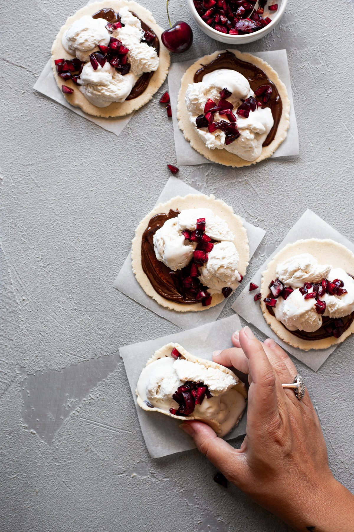 five edible cookie dough dessert tacos with a hand holding one