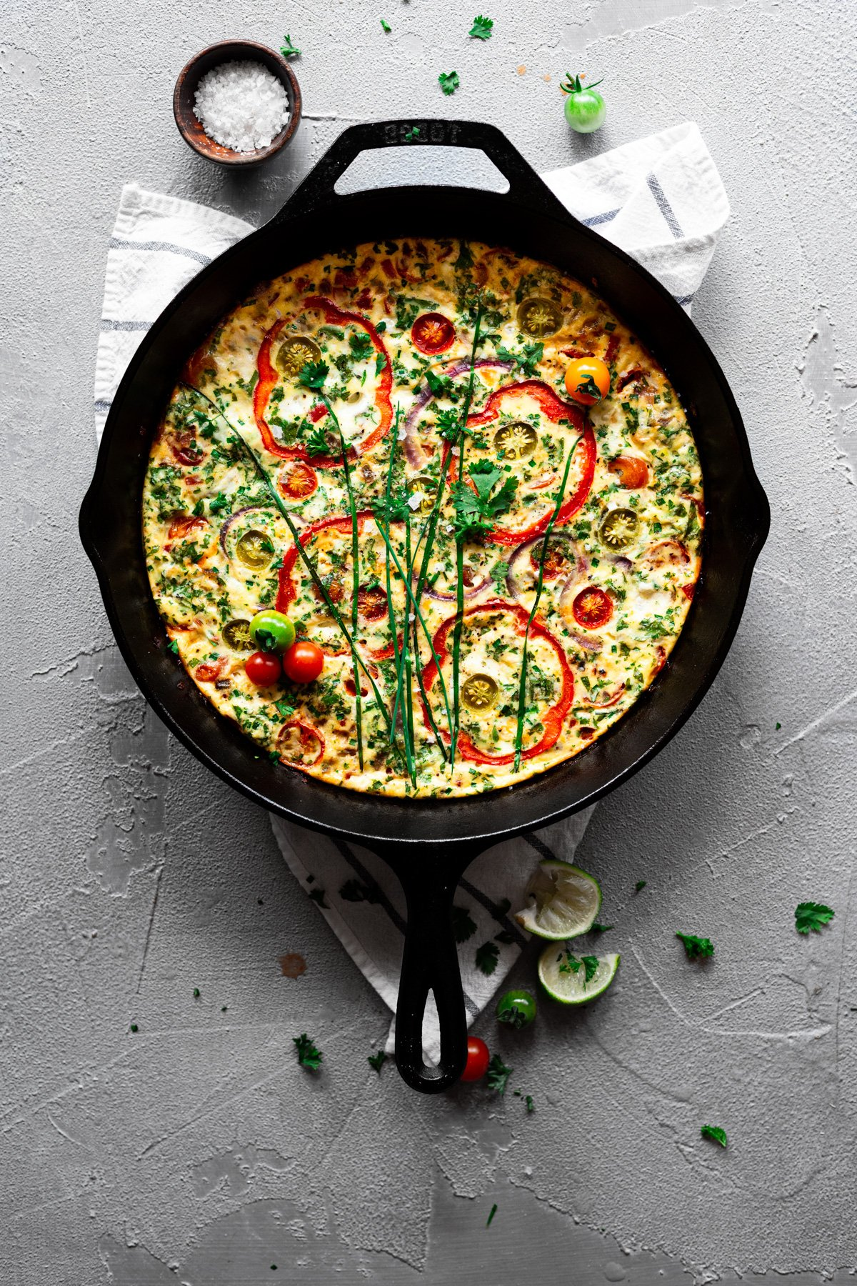 cast iron skilled with easy frittata recipe with veggies, herbs, and cheese