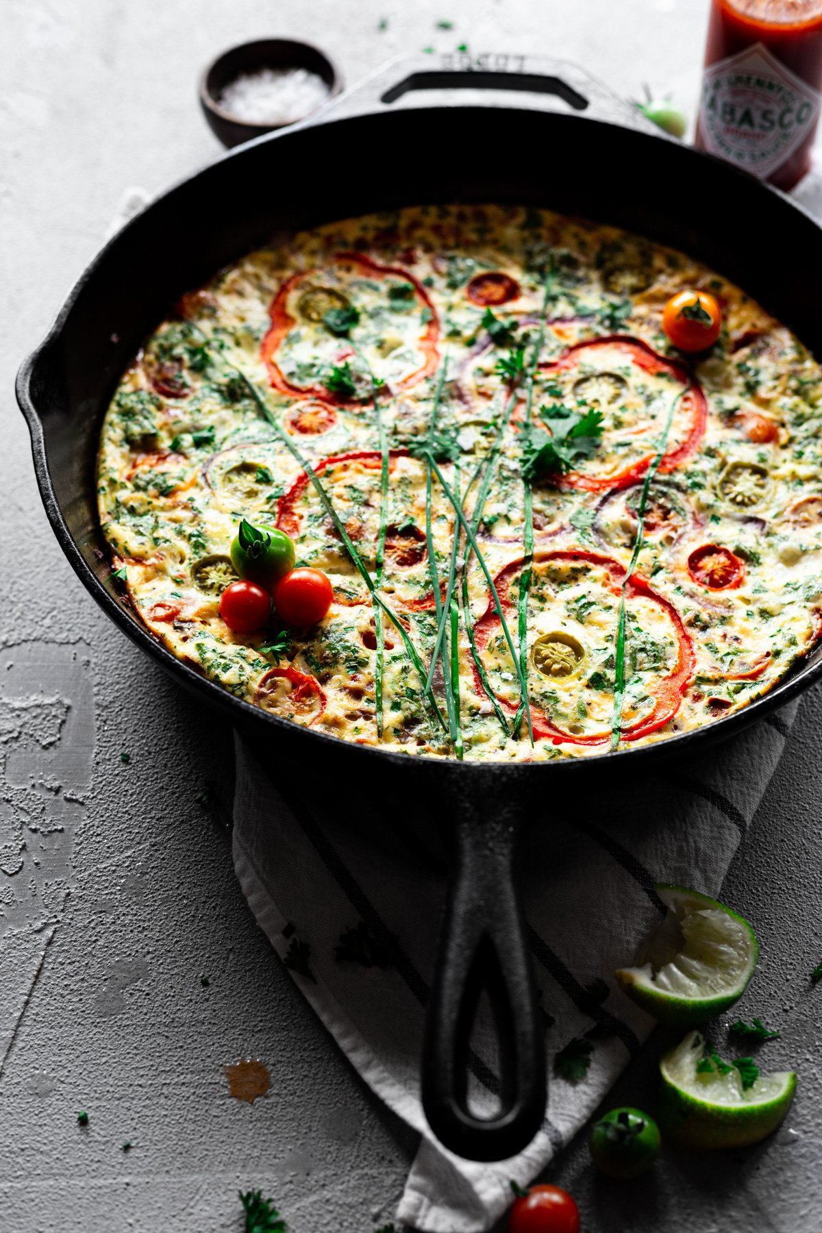 angled view of baked frittata recipe with veggies and herbs