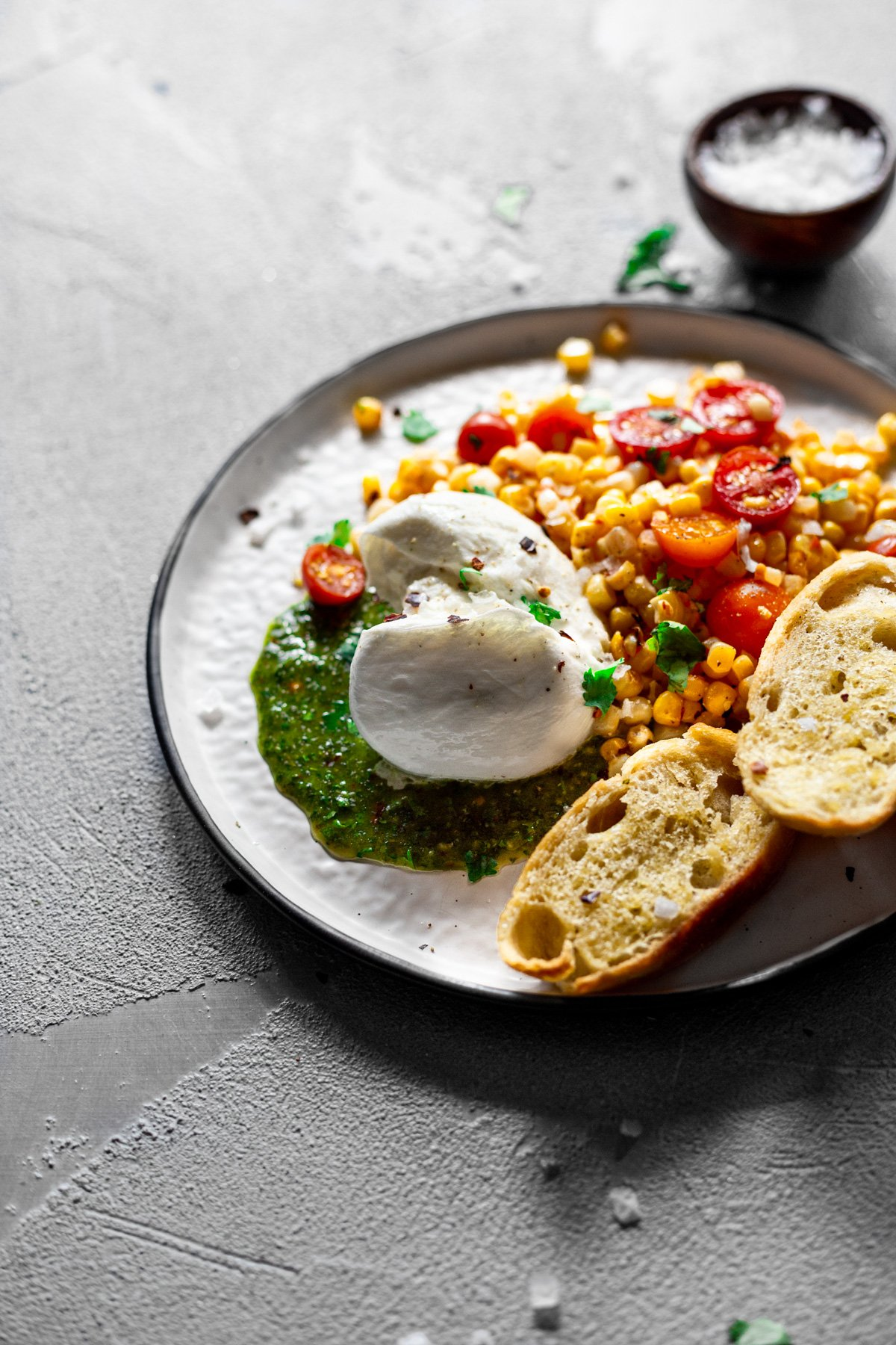 angled view of burrata with chimichurri sauce and corn and tomato salad
