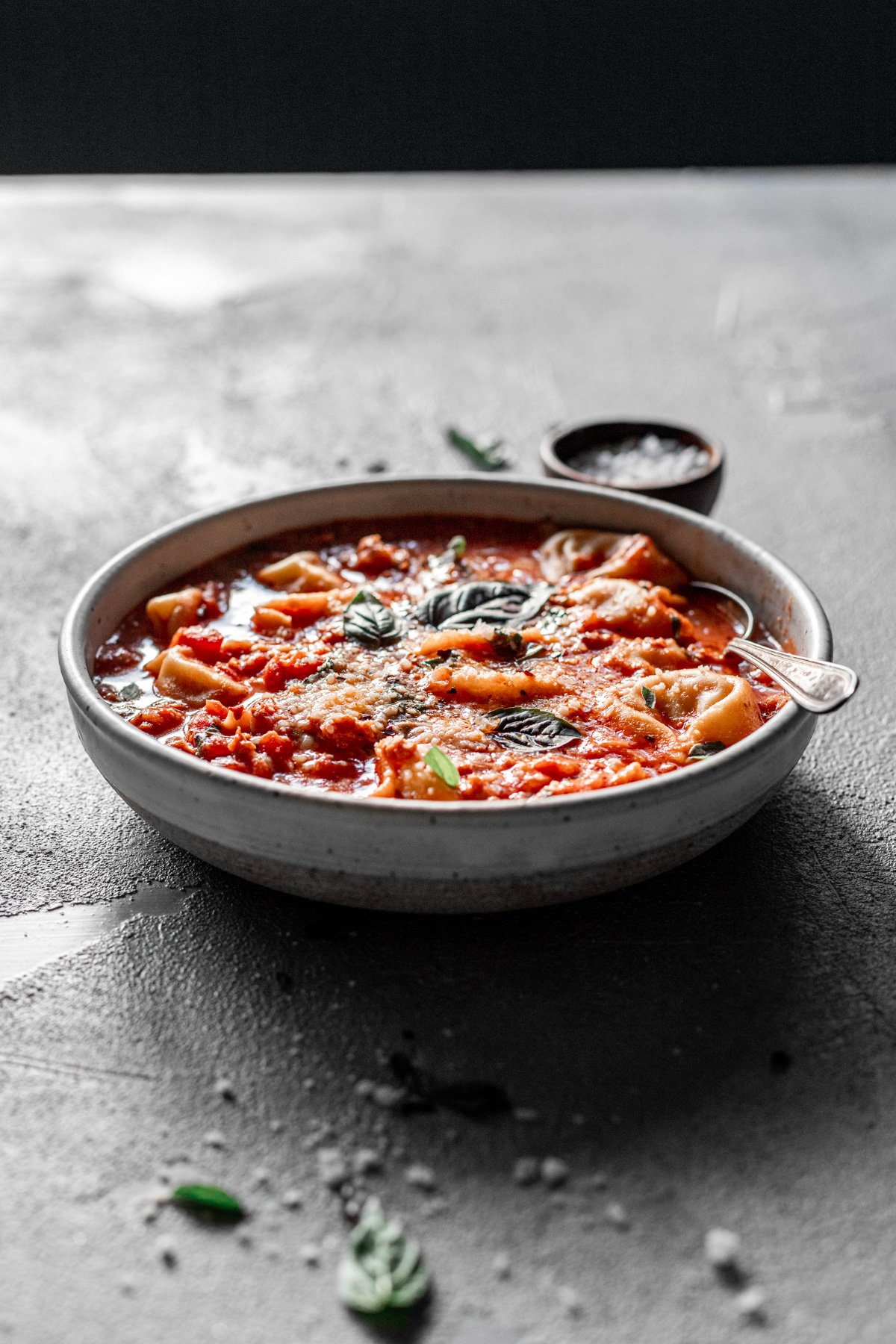 easy tortellini soup recipe in a bowl with fresh basil and parmesan, at an angle