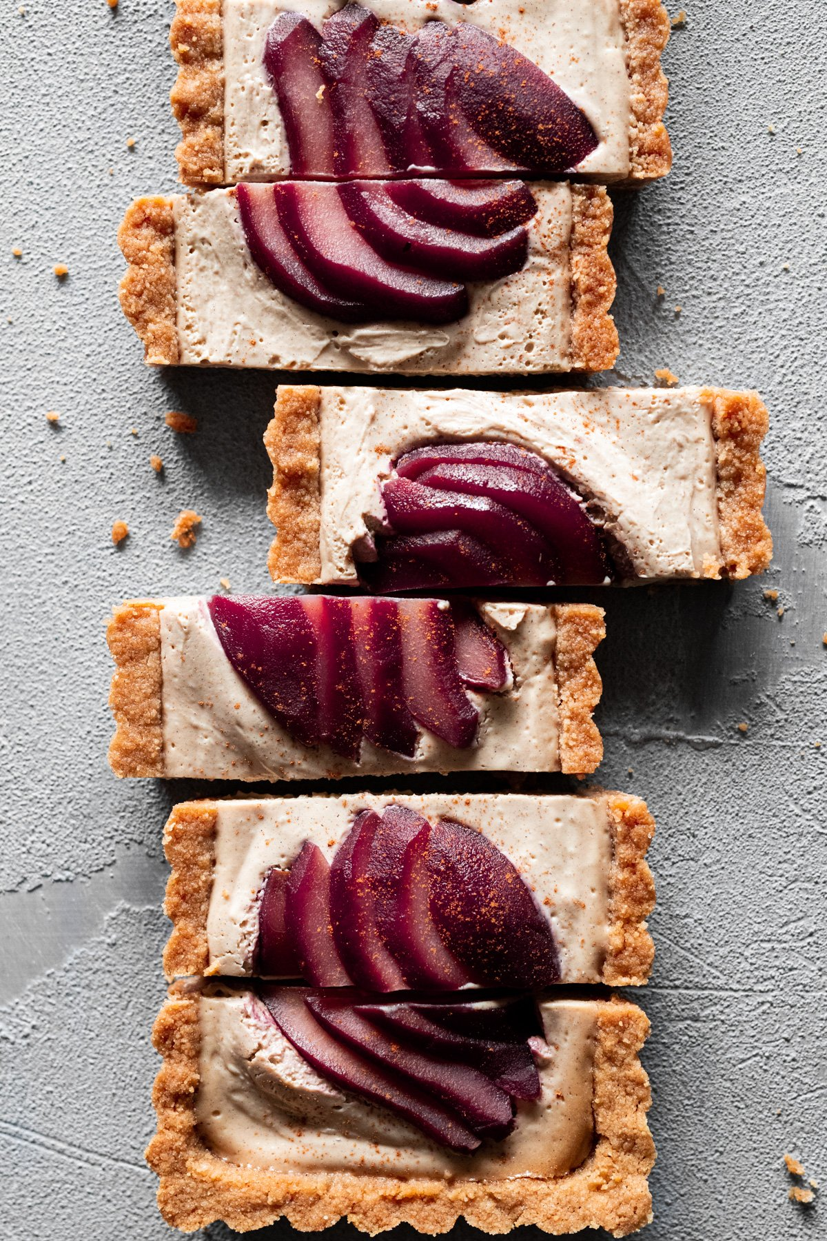slices of fall-spiced vegan tart with wine poached pears on top