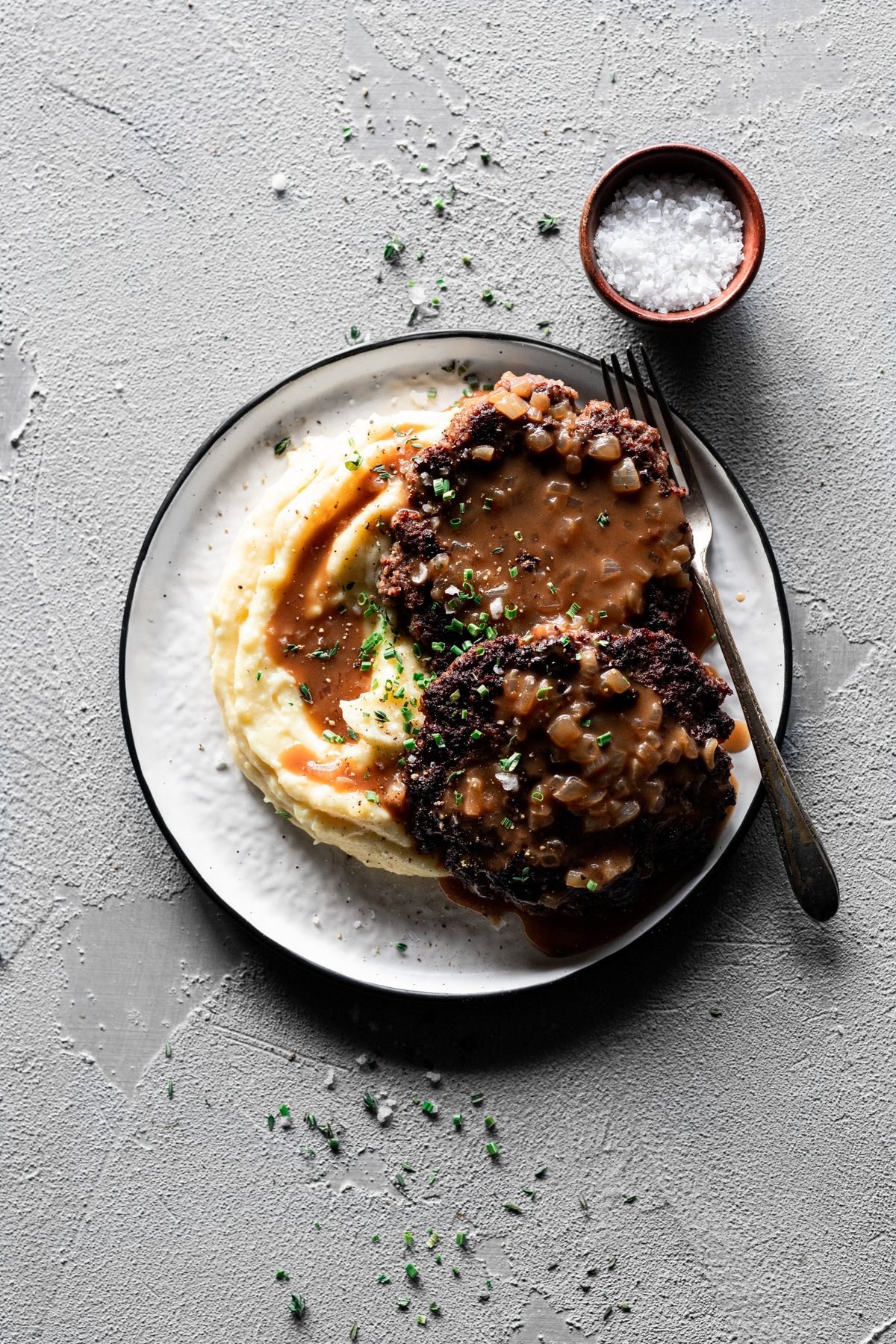 two salisbury steak patties with onion gravy on mashed potatoes