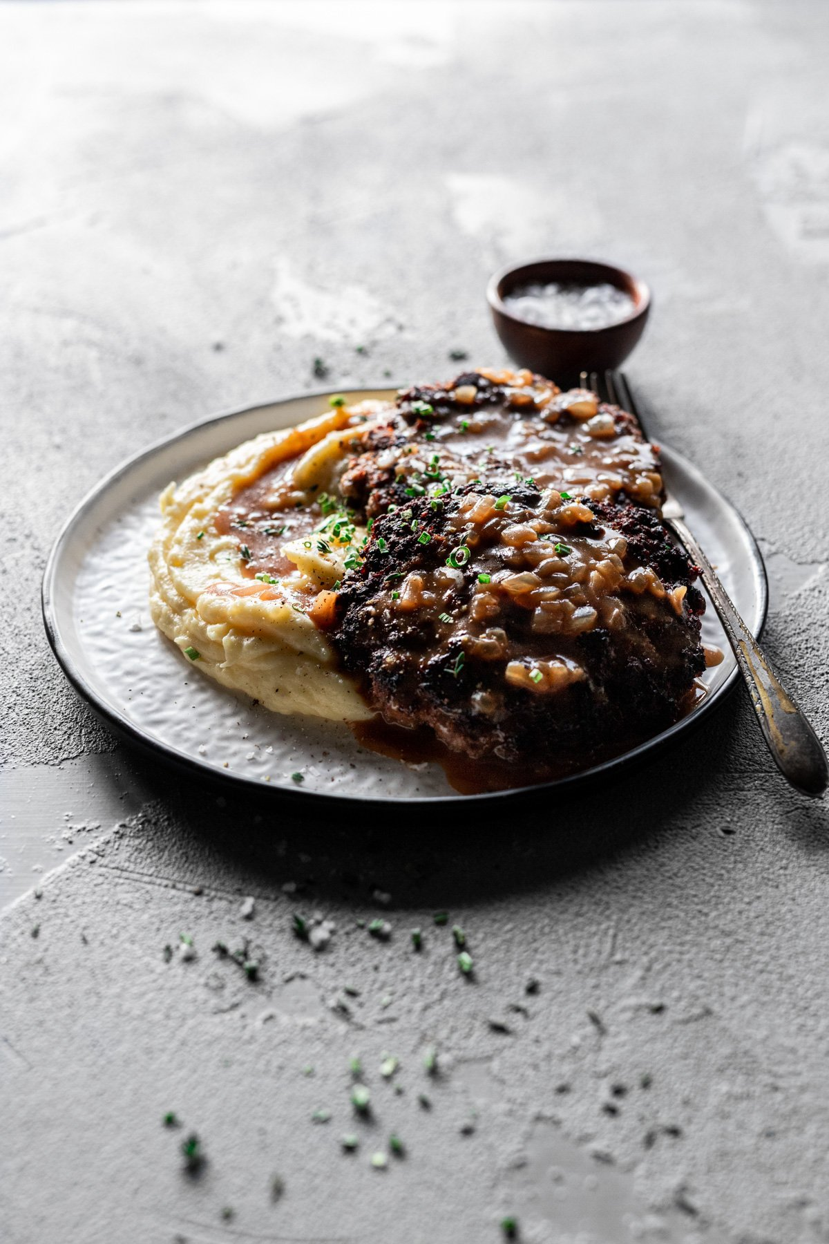 easy salisbury steak with gravy on top of creamy mashed potatoes