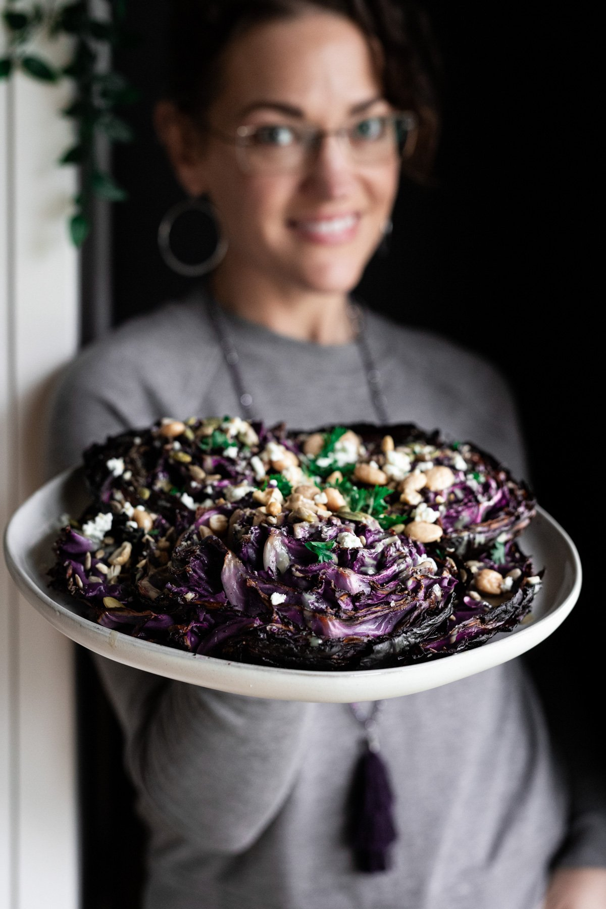 karly gomez holding a plate of roasted red cabbage ready to be served