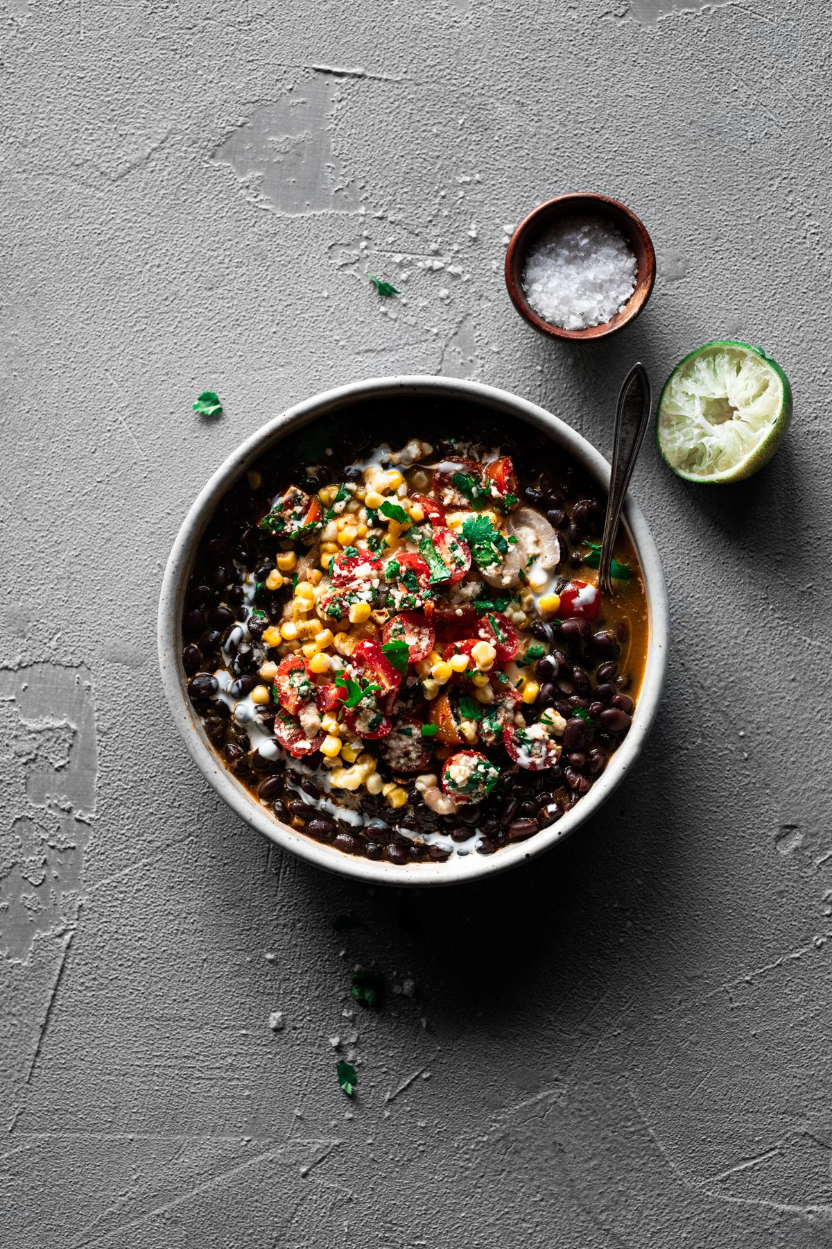 bowl of black bean soup topped with creamy mexican street corn and tomato salsa