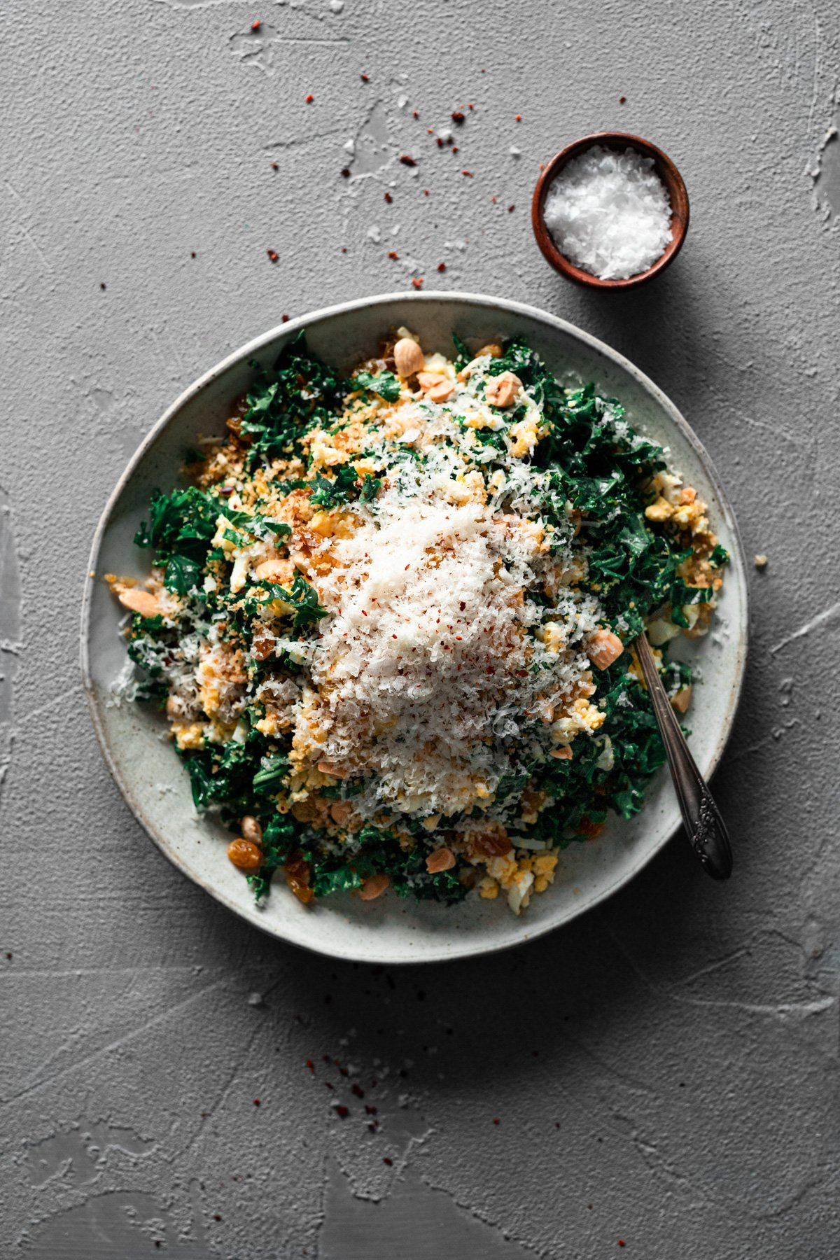 bowl with easy kale salad recipe with marcona almonds, manchego, and aleppo pepper