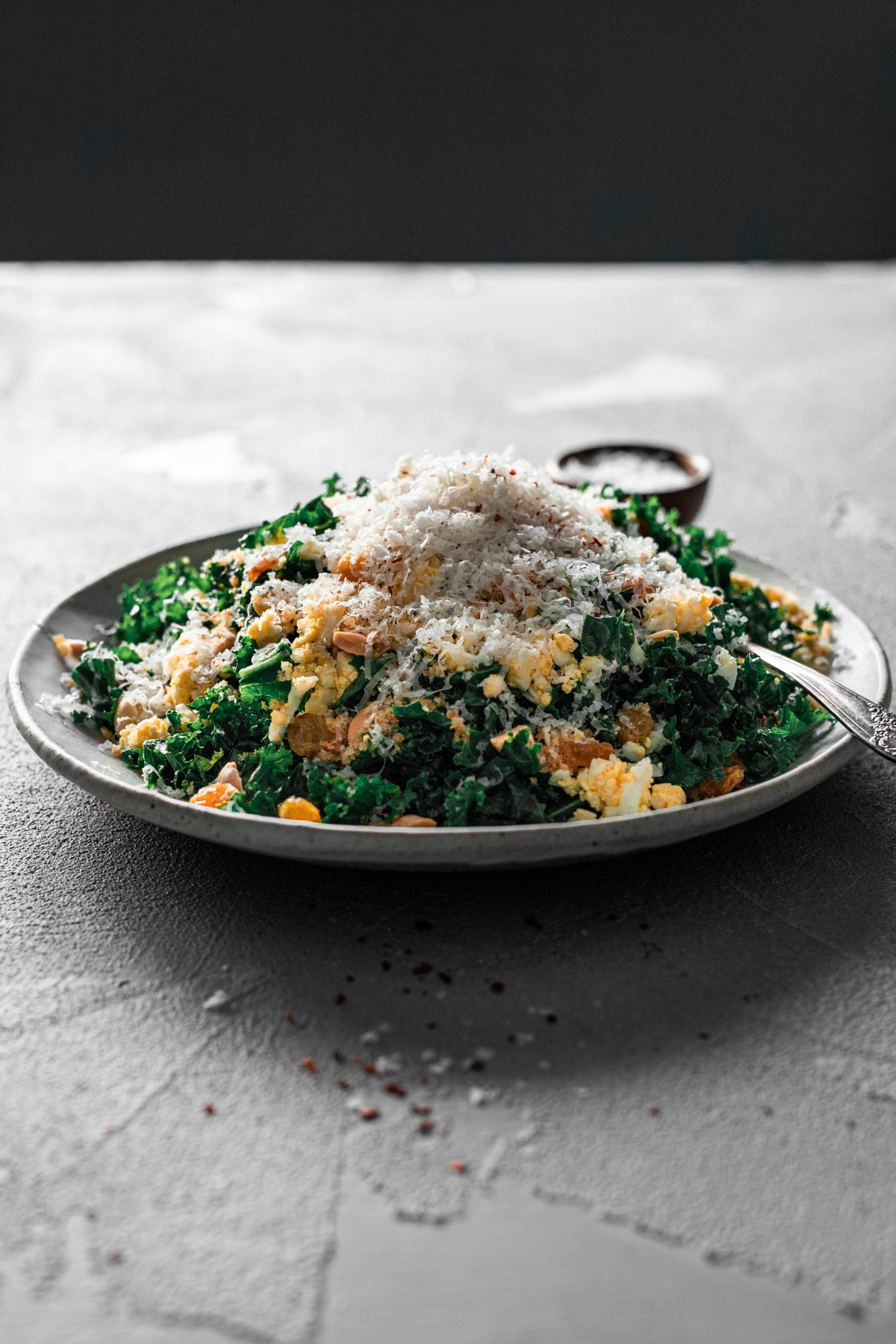 backlit plate of easy kale salad recipe with marcona almonds, manchego, and aleppo pepper