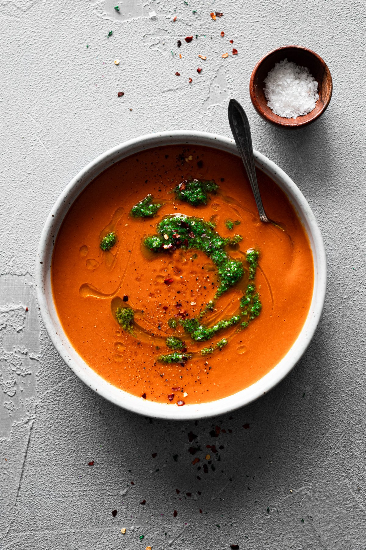 bowl of roasted red pepper soup topped with fresh pesto